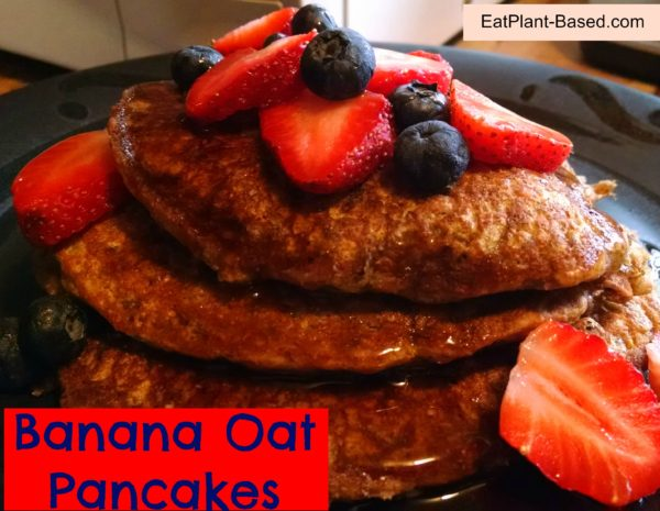 Vegan Banana Oatmeal Pancakes topped with blueberries and strawberries.