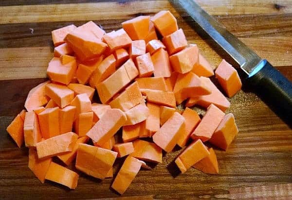 diced sweet potatoes on cutting board with knife