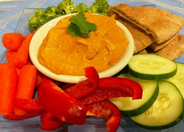 roasted red pepper hummus in bowl with plate of vegetables
