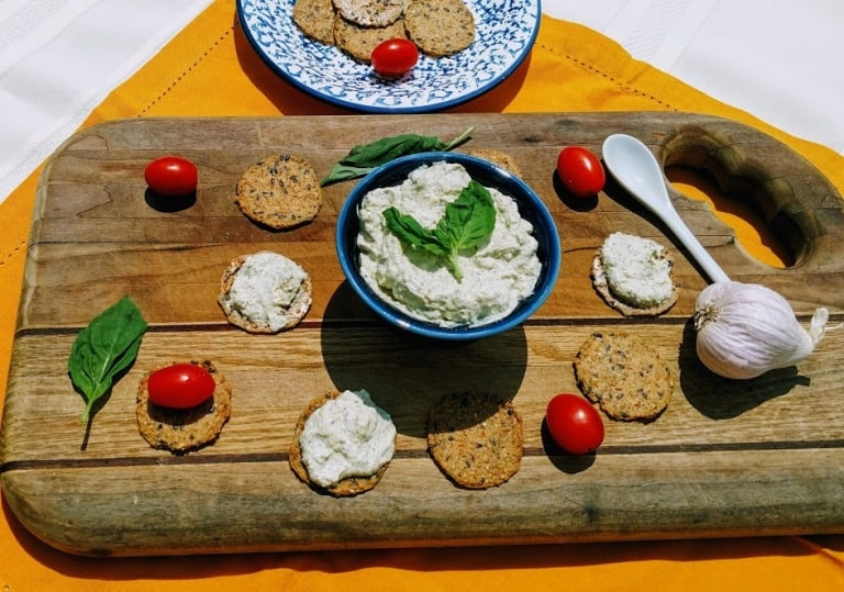 vegan ricotta in blue bowl. crackers and tomatoes on cutting board.