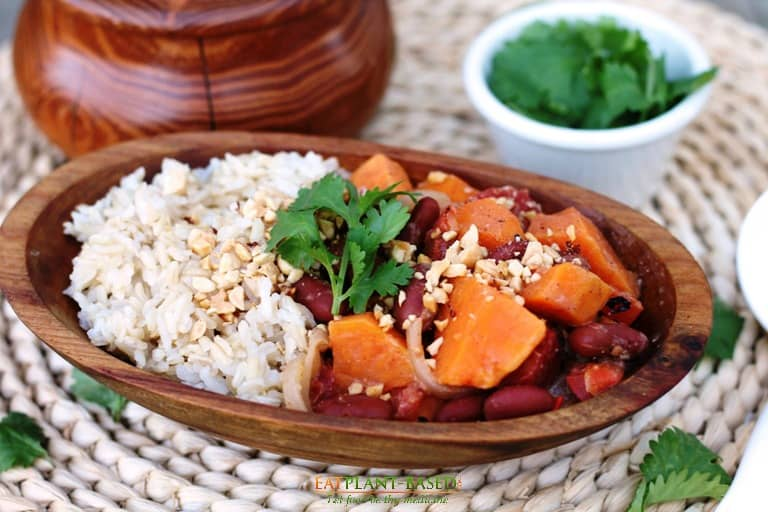 african sweet potato peanut stew with rice in wooden bowl