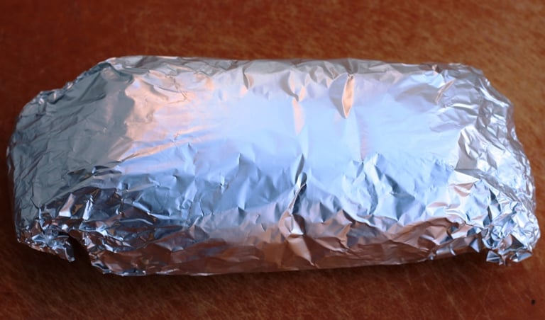 Mushroom loaf wrapped in parchement paper then foil for baking.
